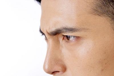 眉間にしわを寄せる男性