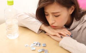頭痛薬を飲むか迷っている女性